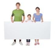 Family in sportswear holding blank billboard. Full length portrait of family in sportswear holding blank billboard against white background Stock Photo