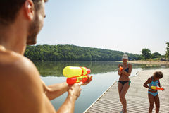 Family spray each other with squirt guns in summer Royalty Free Stock Images