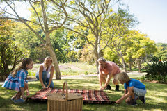 Family spreading the picnic blanket. In park Royalty Free Stock Photo