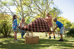 Family spreading the picnic blanket. In park Stock Photo