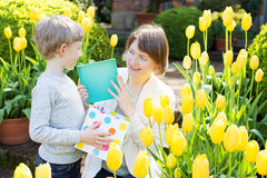 Family at spring. Cheerful son gives her young mother present for mother's day in the park at spring time by the blooming tulips Stock Images
