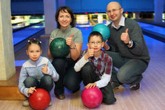 Family of squatting in bowling club. And shows  hands of ok, focus on children Stock Photo