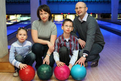 Family of squatting in club for bowling. Family from four persons  of squatting in club for bowling and holds on to balls, focus on children and balls Royalty Free Stock Images