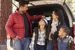 Family stand at the open back of their car before a hike Stock Images