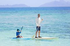 Family stand up paddleboarding. Family of two, little boy and young father, enjoying stand up paddleboarding together, active family vacation concept Stock Image