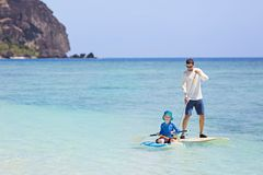 Family stand up paddleboarding. Family of two, little boy and young father, enjoying stand up paddleboarding together at fiji, active family vacation concept Stock Photos