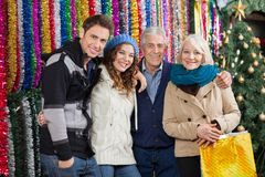 Family Standing Against Tinsels At Christmas Store Royalty Free Stock Image