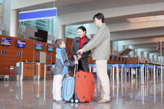 Family standing in airport hall with suitcases royalty free stock photography