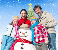 Family Standing Around Snowman And A Christmas Tree Behind Them Royalty Free Stock Photography