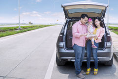 Family standing behind car Stock Photos