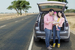 Family standing behind car with tablet Royalty Free Stock Photography