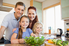 Family standing behind the kitchen counter Stock Photo