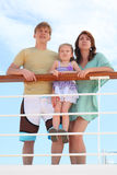 Family standing on cruise liner deck near rail. Family with daughter standing on cruise liner deck near rail, child standing on fence royalty free stock image