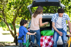 Family standing in front of a car Royalty Free Stock Photos