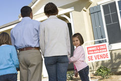 Family Standing In Front Of House For Sale Stock Photo