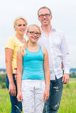 Family standing on grass of lawn or field Stock Photos