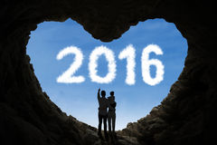 Family standing inside cave with numbers 2016 Royalty Free Stock Image
