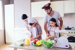Family is standing in kitchen and cooking. Guy helps girl to cut cucumber. Woman stands behind her son and look at how. Happy men and women stand in kitchen and Royalty Free Stock Photos