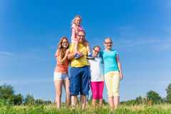 Family standing on meadow - father with children Stock Image