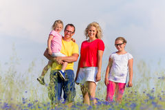 Family standing on meadow in summer with flowers Royalty Free Stock Photo
