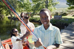 Family standing in motorboat, focus on boy (8-10) standing on lake jetty, holding fishing rod, smiling, portrait Stock Images