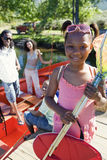 Family standing in motorboat, focus on girl (7-9) standing on lake jetty, holding fishing net, smiling, portrait Stock Images
