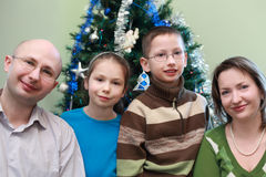 Family standing near Christmas tree. Father, mother, son and daughter standing near Christmas tree, happy family, focus on girl Stock Photo