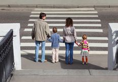 Family standing near crossover, behind. Mother and father holds hand of little daughter and son and standing near crossover, behind Stock Photo