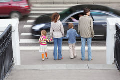 Family standing near pedestrian crossing. Mother and father holds hand of little daughter and son and standing near pedestrian crossing, behind, two cars on road Stock Photography