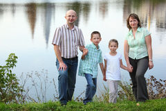 Family is standing near pond in park Royalty Free Stock Image