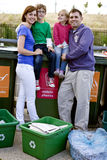A family standing next to recycling bins Stock Images