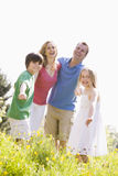 Family standing outdoors holding hands smiling Stock Images