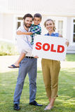 Family standing outside home with sold sign Stock Photography