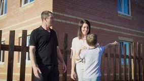 Family standing outside house. Proud mother and father with young son. Residential area stock footage