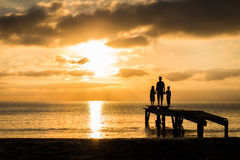 Family standing on the pier watching sunrise Stock Photos