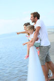 Family standing on a pontoon watching the sea Stock Photos