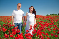 Family standing in poppy field smiling Royalty Free Stock Photo