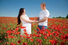 Family standing in poppy field smiling Royalty Free Stock Images