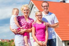 Family standing proud in front of home Stock Photo