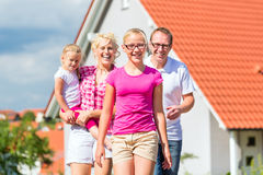 Family standing proud in front of home Stock Images