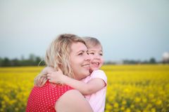 Family standing in rapeseed field and smiling Royalty Free Stock Images