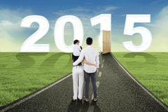 Family standing on the road to future. Young family embracing on the road and walk together towards future 2015 Stock Photos