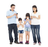 Family standing a row and using smart phone together Royalty Free Stock Image