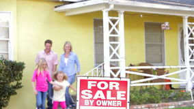 Family Standing By For Sale Sign Outside Home stock video