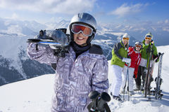 Family standing in snow on mountain top with skis stock image