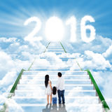 Family standing on the stairs with numbers 2016 Royalty Free Stock Photo
