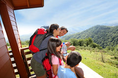 Family standing on terrace of cabin admiring nature Stock Photography
