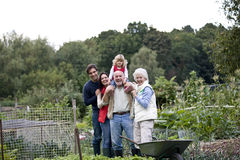 A family standing together on an allotment, laughing Stock Photos