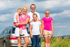 Family standing together in front of car royalty free stock photography