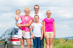 Family standing together in front of car stock photography